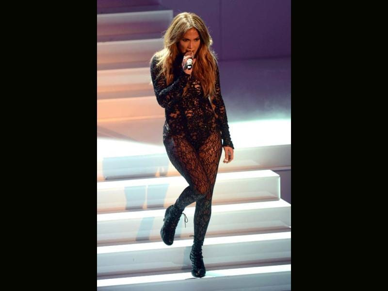 Curves personified, JLo poured herself into a fitting lacy black outfit, teamed with matching stockings.