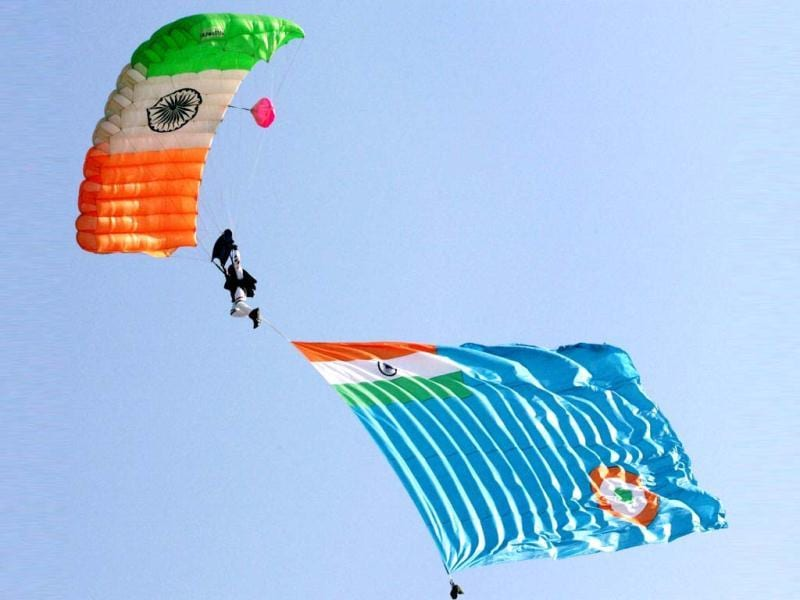 An IAF person carries the force's flag as he descends with a parachute during 80th Air Force Day celebrations at Air Force Station in Hindon. PTI Photo