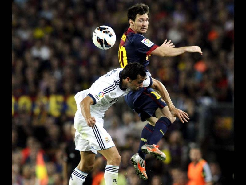 Barcelona's Lionel Messi and Real Madrid's Alvaro Arbeloa fight for the ball during their Spanish first division soccer match at Nou Camp stadium in Barcelona. (Reuters)