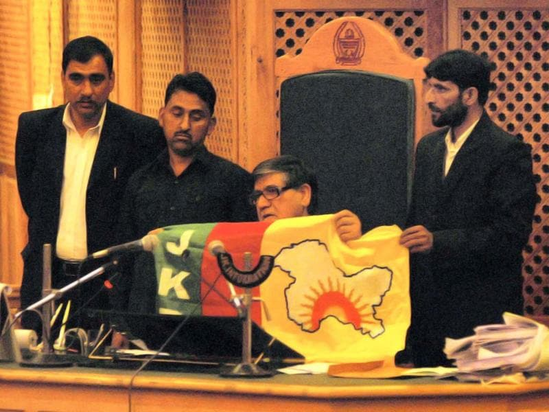 Speaker Mohammad Akbar Lone displays the flag that was carried by an intruder in Jammu and Kashmir assembly in Srinagar. PTI