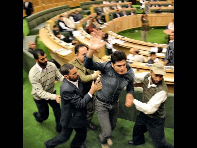 Watch and Ward staff take away a youth who entered Jammu and Kashmir assembly demanding implementation of employment policy, in Srinagar. PTI