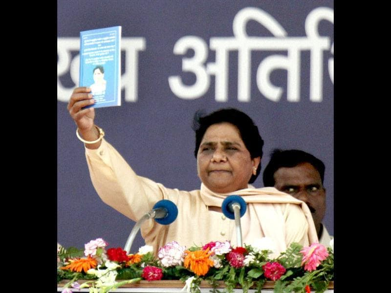 BSP supremo Mayawati shows a book while addressing a party rally on the occasion of party founder Kanshiram's sixth death anniversary in Lucknow. PTI Photo
