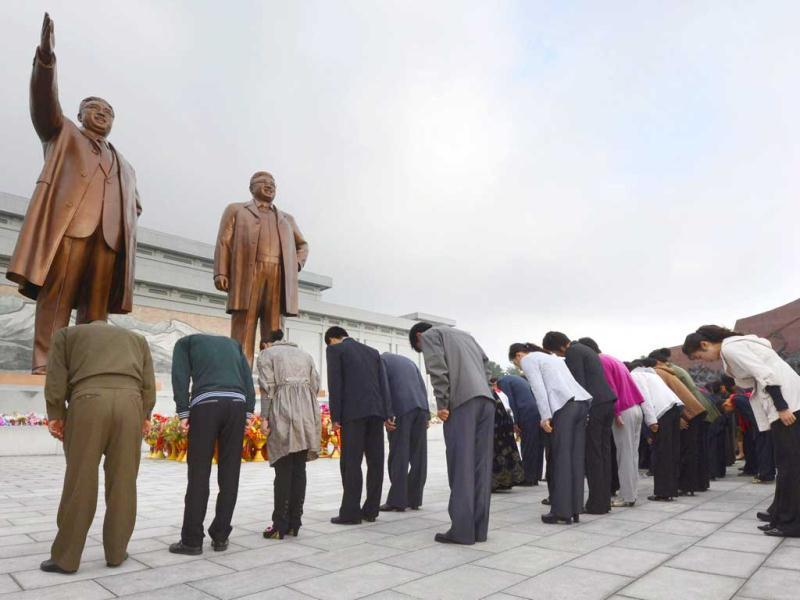 North Koreans bow in front of the statues of the country's founding ruler Kim Il Sung, left, and his son and successor Kim Jong Il to mark the 67th founding anniversary of the ruling Workers' Party of Korea, in Pyongyang, North Korea. AP/Kyodo News