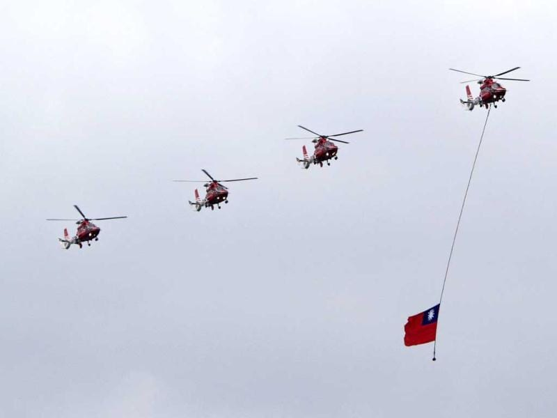 A team of rescue helicopters drag a Taiwanese national flag during National Day celebrations marking the 101st anniversary of the founding of the Republic of China, in front of the Presidential Office in Taipei, Taiwan. AP Photo/Chiang Ying-ying