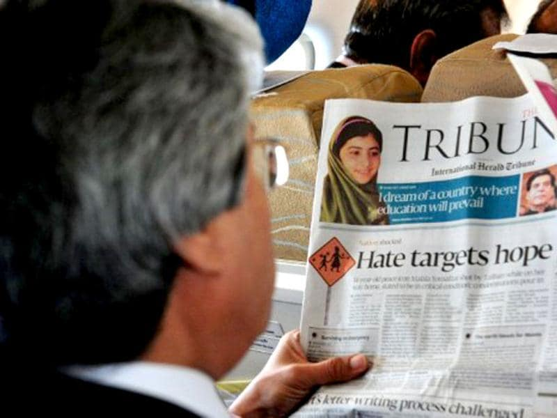 A Pakistani passenger reads a local newspaper featuring news of Malala Yousafzai during a flight over Pakistan, a day after Yousafzai was shot in the head in an assassination attempt. AFP /Farooq Naeem