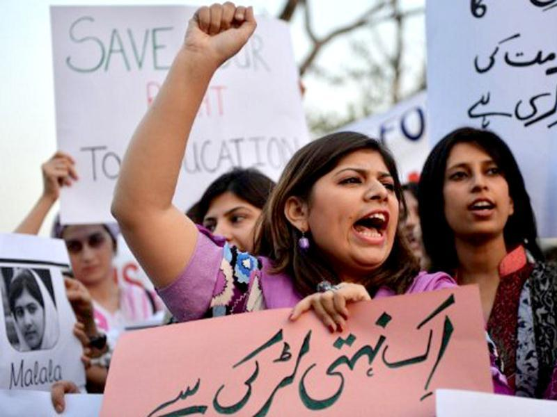 Pakistani civil society activists carry placards with a photograph of the gunshot victim Malala Yousafzai as they shout ant-Taliban slogans during a protest rally against the assassination attempt on Malala Yousafzai, in Islamabad .AFP / Aamir Qureshi