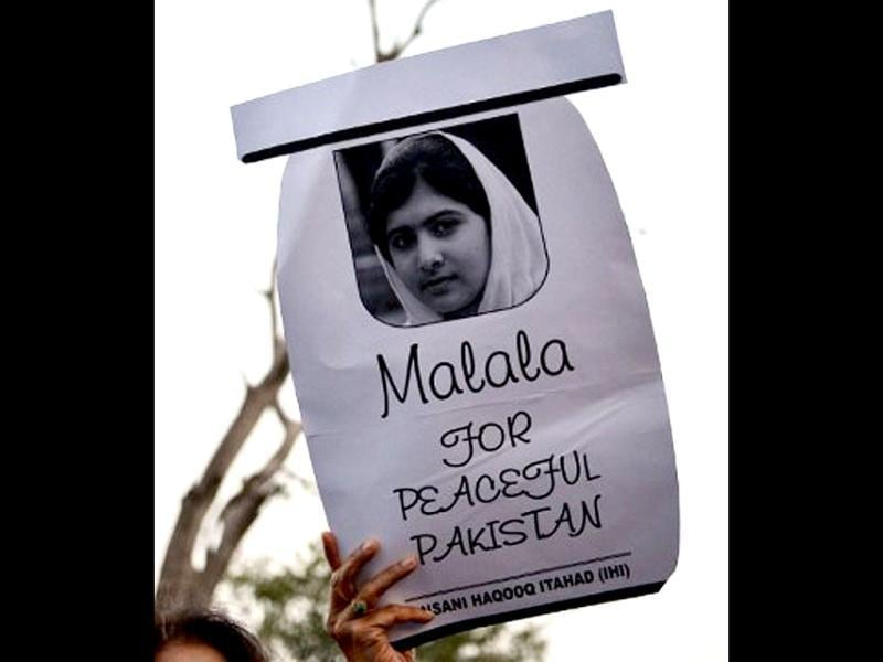 A Pakistani civil society activist carries a placard with a photograph of gunshot victim Malala Yousafzai as they shout ant-Taliban slogans during a protest rally against the assassination attempt on Malala Yousafzai, in Islamabad. AFP / Aamir Qureshi