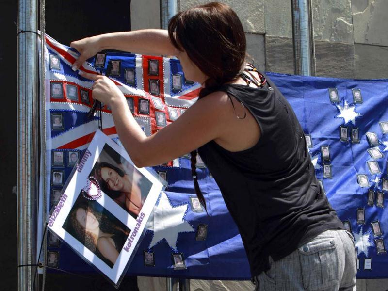 A girl attaches a picture of her friend to an Australian flag alongside other pictures of Australians who died during 2002 Bali bombing memorial monument, ahead of the 10-year anniversary of the incident in Kuta, Bali resort island, Indonesia. Reuters Photo