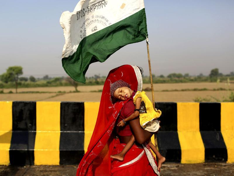 Landless farmer woman carries her child and marches during the