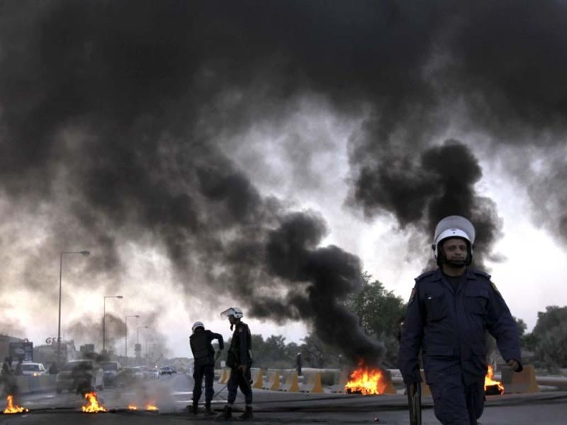 Riot police extinguish burning tires set by Bahraini anti-government protesters, unseen, near oil pipelines that connect to neighboUring Saudi Arabia along a highway in Buri, Bahrain. AP photo