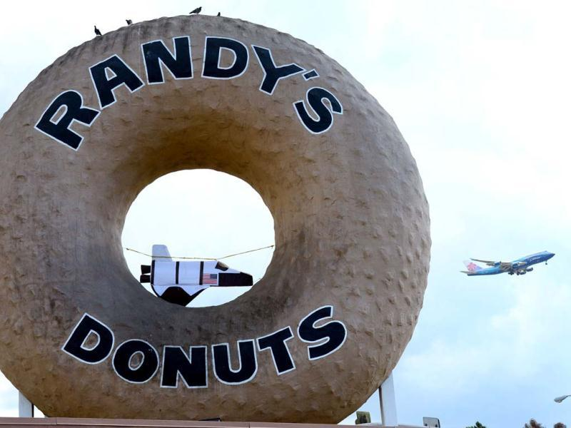 An airplane passes the giant donut on the roof of Randy's Donuts where a mini US Space Shuttle is strung up in the donut hole in Inglewood, in southwest Los Angeles County, California, along the route the US Space Shuttle Endeavour will pass in coming days. AFP photo
