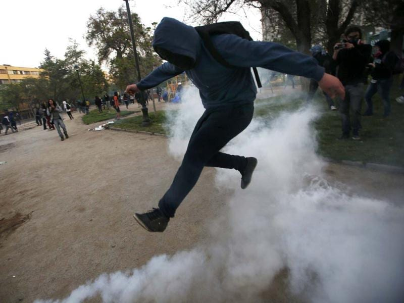 A student protester jumps to avoid a tear gas canister during a protest against the government to demand changes in the public state education in Santiago. Reuters photo