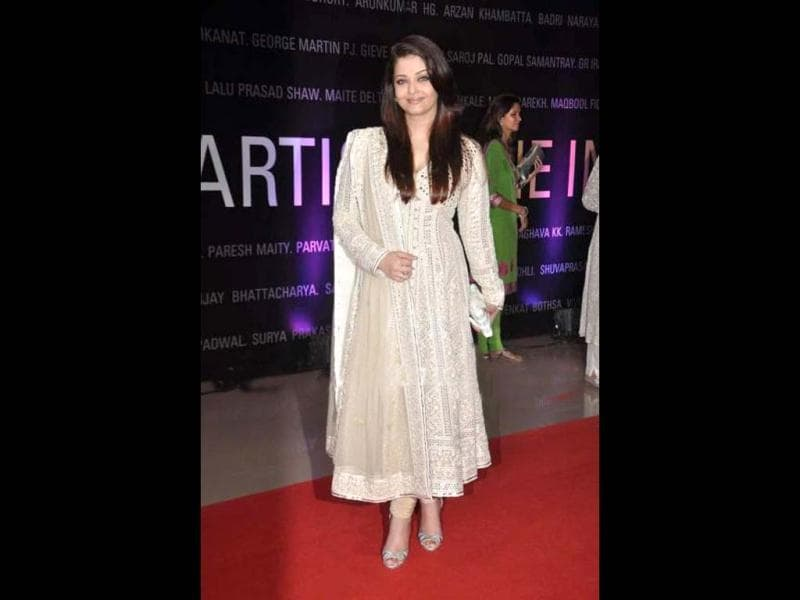 Aishwarya Rai Bachchan stuns in a beige Anarkali suit as she poses a subtle smile at the event.
