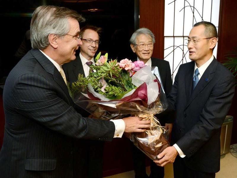 This photo shows Kyoto University professor Shinya Yamanaka receiving a flower bouquet from Sweden's ambassador to Japan Lars Vargo in Kyoto, western Japan after it was announced that Yamanaka won the Nobel Medicine Prize. AFP/Jiji Press