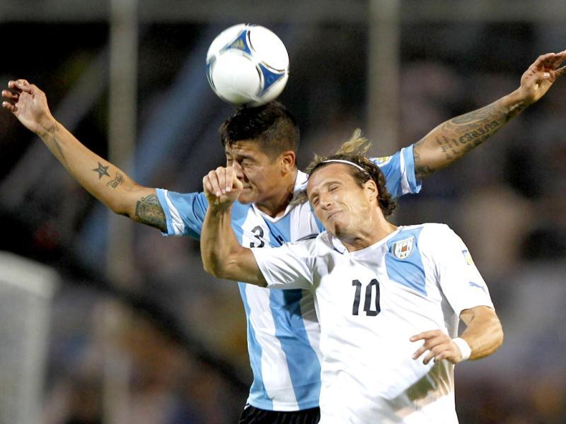 Diego Forlan (R) of Uruguay battles for the ball with Marcos Rojo of Argentina during their 2014 World Cup qualifying soccer match in Mendoza. Reuters photo