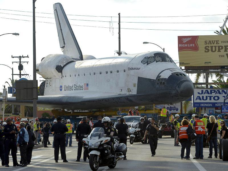 The Space Shuttle Endeavour turns a corner as it is slowly moved along city streets in Los Angeles. The shuttle is on its last mission Ñ a 12-mile creep through city streets. It will move past an eclectic mix of strip malls, mom-and-pop shops, tidy lawns and faded apartment buildings to its final destination - California Science Center in South Los Angeles where it will be put on display. AFP photo