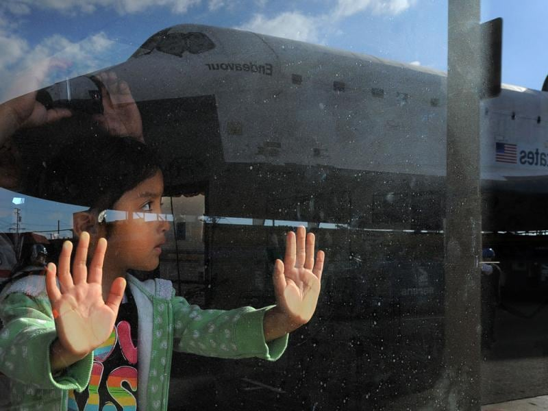 Space shuttle Endeavour is seen reflected in a window on route from Westchester square to Randy's Donuts during its final ground journey in Los Angeles. AP photo