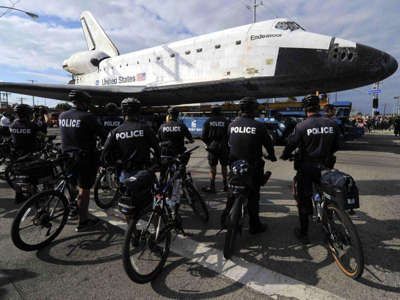 Policemen watch space shuttle Endeavour as it makes its way from Westchester square to Randy's Donuts during its final ground journey in Los Angeles, California. Reuters photo