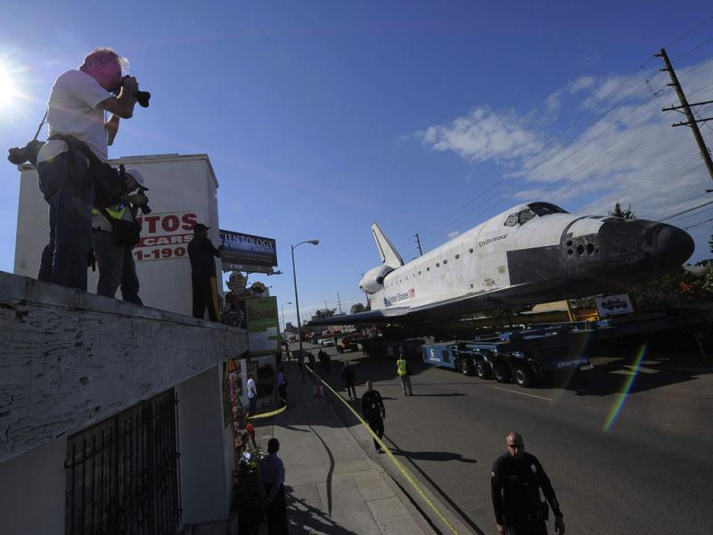 A man takes photographs of space shuttle Endeavour as it makes its way from Westchester square to Randy's Donuts during its final ground journey in Los Angeles, California. Reuters photo