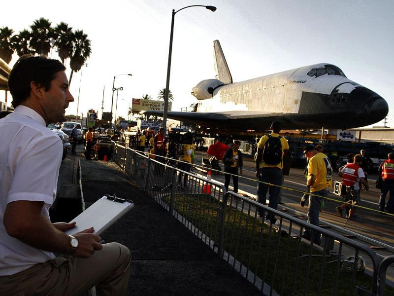 Actor Luke Wilson sits near space shuttle Endeavour on Manchester Avenue while it is being moved from Los Angeles International Airport to its retirement home at the California Science Center in Exposition Park, in Los Angeles. Reuters photo