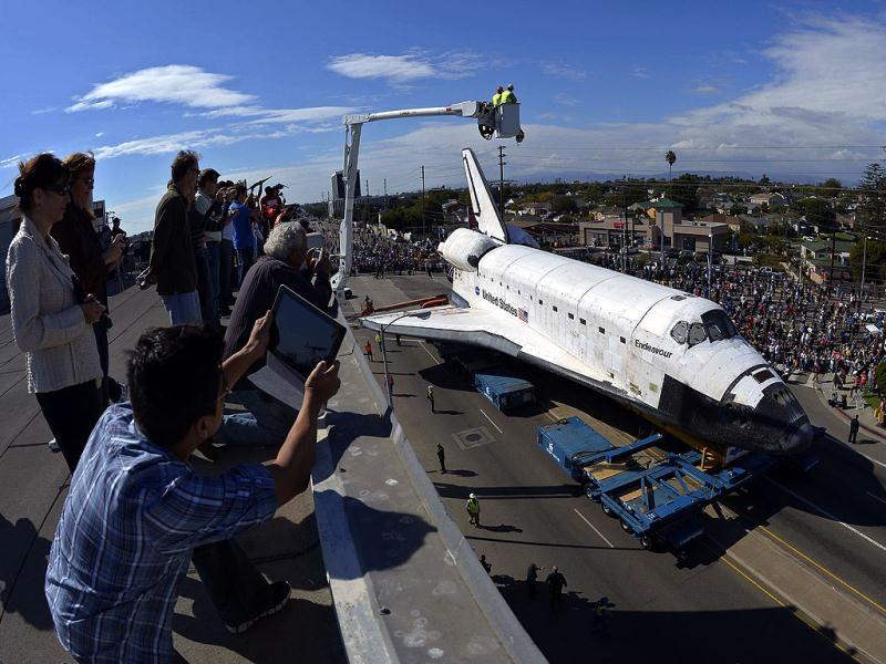 People take pictures from the roof of a building as the space shuttle Endeavour is slowly moved along city streets in Los Angeles. Reuters photo