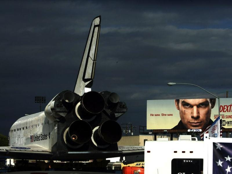 The space shuttle Endeavour makes its way east down Manchester Boulevard under the eyes of a Dexter billboard in Westchester, California. Reuters photo