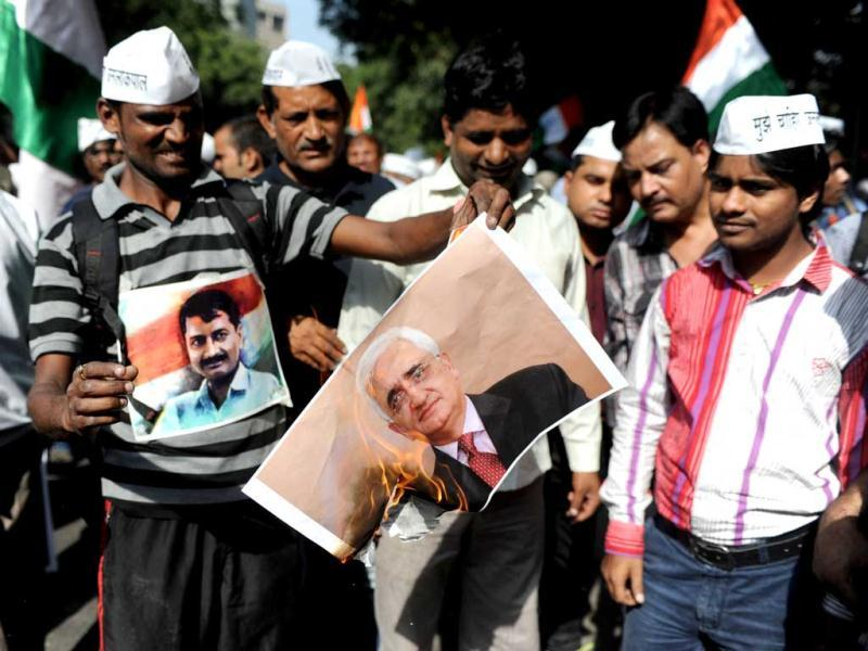 Supporters of Arvind Kejriwal burn a picture of Union law minister Salman Khurshid at Jantar Mantar in New Delhi. AFP Photo