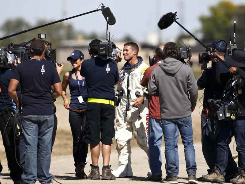 Felix Baumgartner walks with his girlfriend Nici Oetl, facing at left, after Baumgartner successfully jumped from a space capsule in Roswell, New Mexico. AP/Ross D Franklin