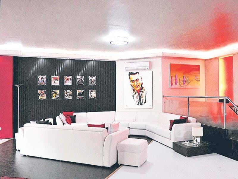 The spacious living room has white couches and posters of Salman on its walls.