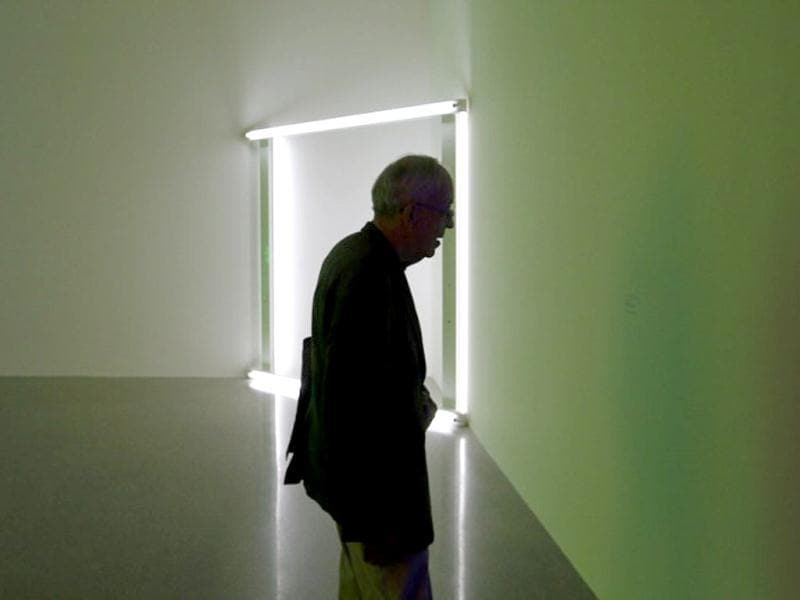 A man reads about the fluorescent tube artwork creations by US artist Dan Flavin as part of the