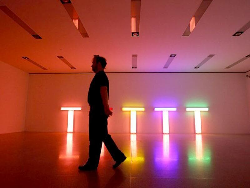 A man walks past fluorescent tube artwork creations by US artist Dan Flavin as part of the