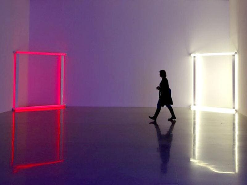 A woman walks past fluorescent tube artwork creations by US artist Dan Flavin as part of the