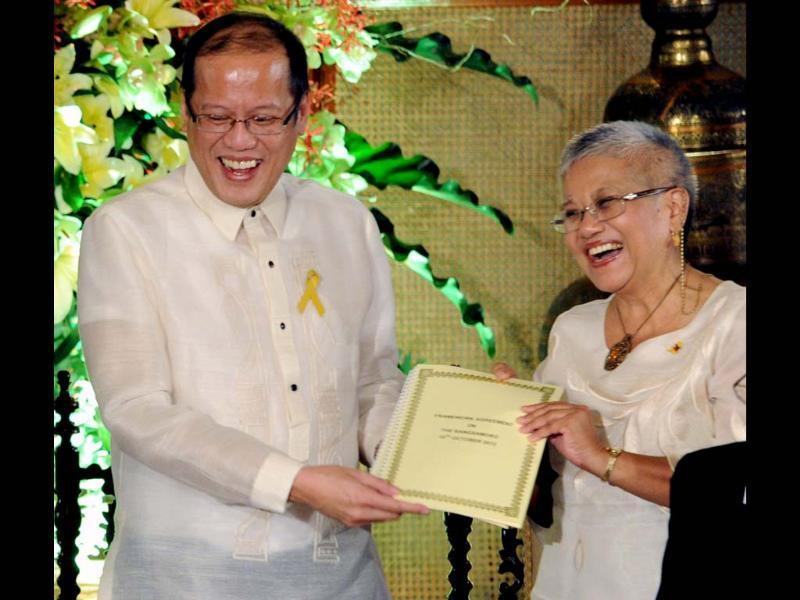 Philippine President Benigno Aquino and Government peace negotiator Teresita Deles, smile as they hold a signed document of the frame works of agreement for peace at Malacanang Palace in Manila. AFP/Jay Directo