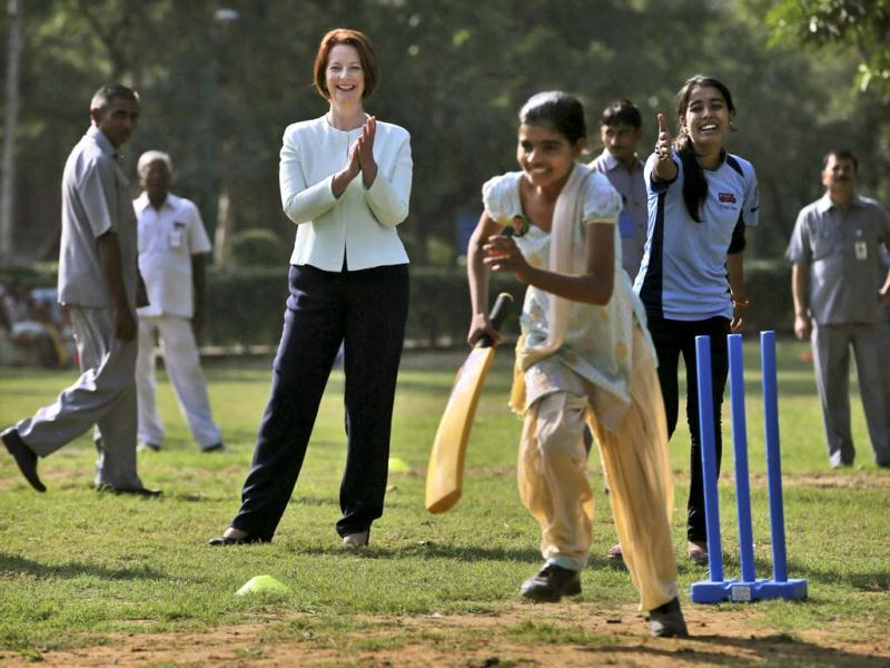 Australia's Prime Minister Julia Gillard, center, applauds as she watches girls play cricket at a camp in New Delhi. Gillard is on a three day official visit to India. (AP Photo)