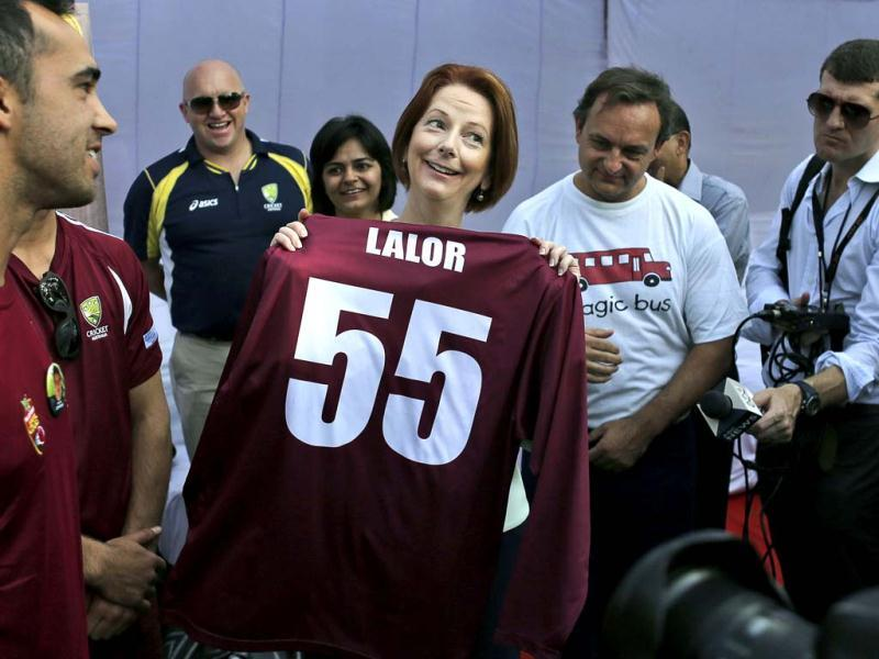 Australia's Prime Minister Julia Gillard, center, holds up a cricket jersey given to her at a camp for underprivileged children in New Delhi. Gillard is on a three day official visit to India. (AP Photo)