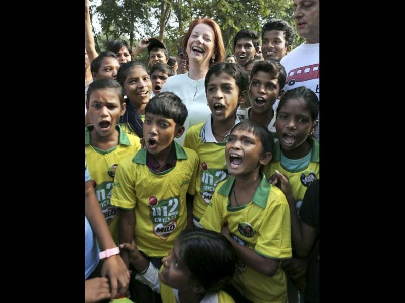 Australia's Prime Minister Julia Gillard, top center, laughs as she poses with underprivileged children at a camp in New Delhi. Gillard is on a three day official visit to India. (AP Photo)