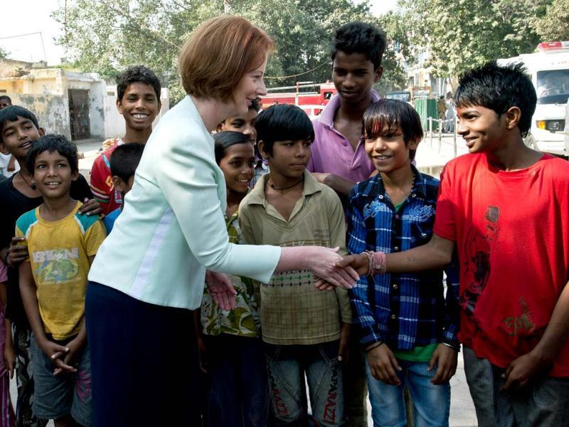Prime Minister of Australia Julia Gillard (C) shakes hands with slum dwelling children during her visit to Asha Education project site to meet students in New Delhi. Australian Prime Minister is on a three day state visit to India. (AFP Photo)