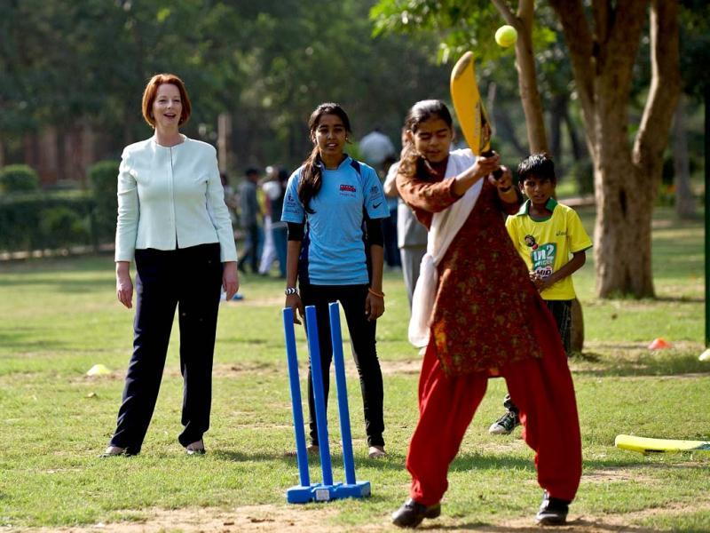 Australian Prime Minister Julia Gillard (L) gestures as she watches Indian girls at a cricket clinic for disadvantaged youth in New Delhi. The Australian Prime Minister is on a three-day state visit to India. (AFP Photo)