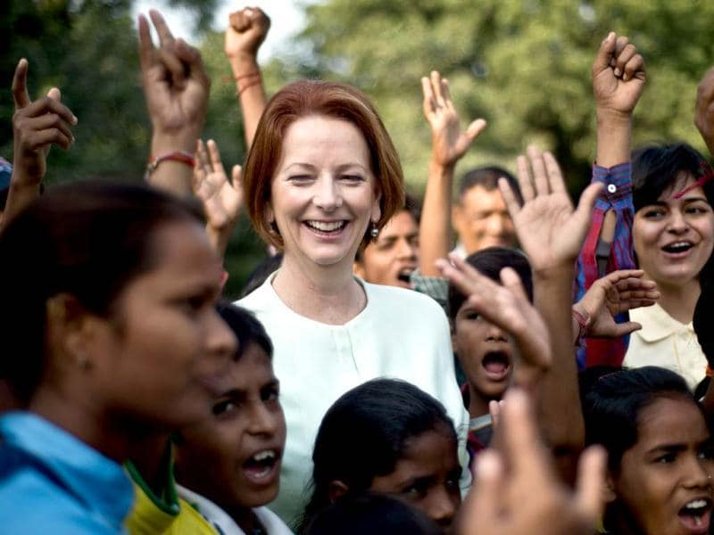 Australian Prime Minister Julia Gillard (C) gestures as she interacts with disadvantaged youth at a cricket clinic in New Delhi. The Australian Prime Minister is on a three-day state visit to India. (AFP Photo)