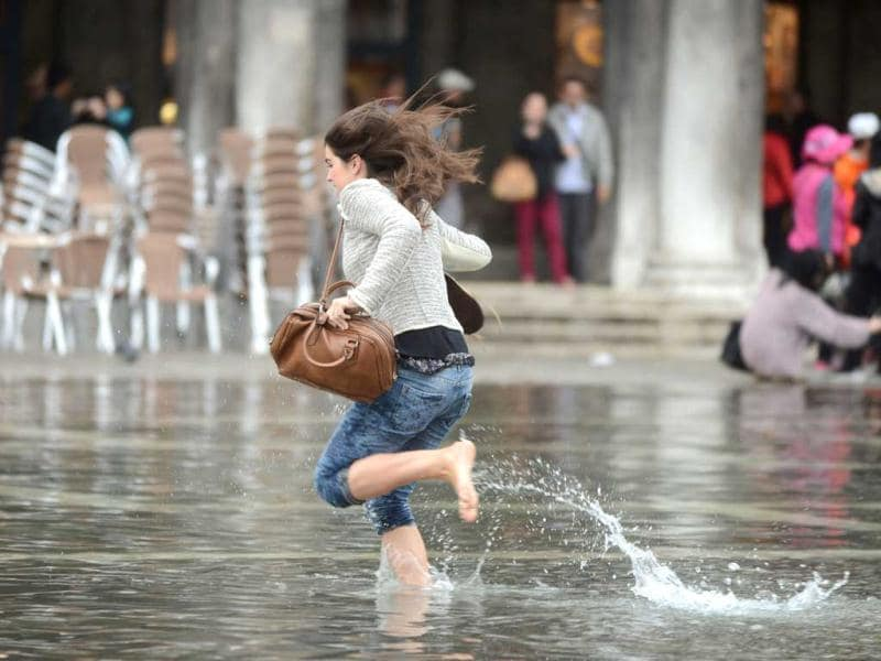 A woman runs in water on a flooded St Mark's square during the first