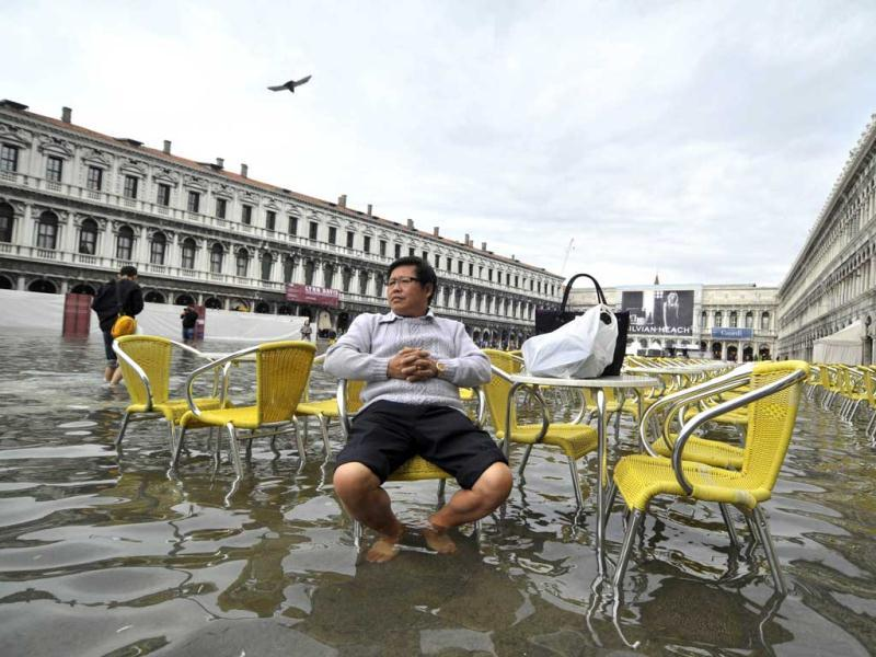 A tourist sits outside a cafe in flooded St. Mark square as high tides reached 1.05 meters above sea level, partly flooding the city of Venice. AP photo