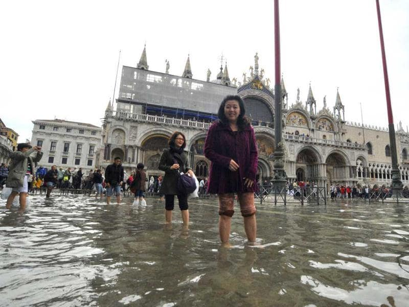 Tourists wade across the flooded St. Mark square as high tides reached 1.05 meters above sea level, partly flooding the city of Venice. AP photo