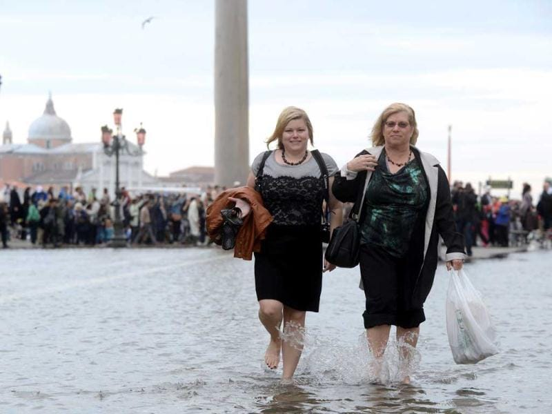 Tourists walk barefoot on a flooded St Mark's square during the first