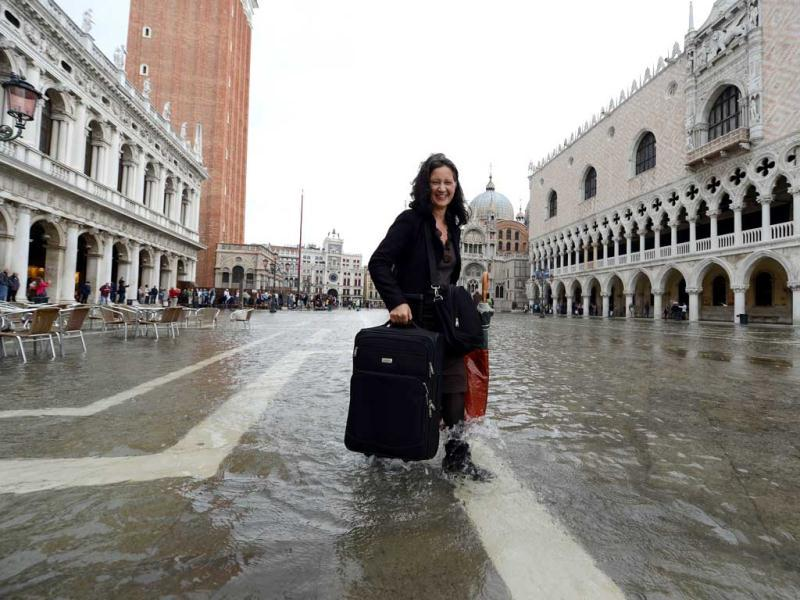 A tourist carries a suitcase as she walks barefoot on a flooded St Mark's square during the first