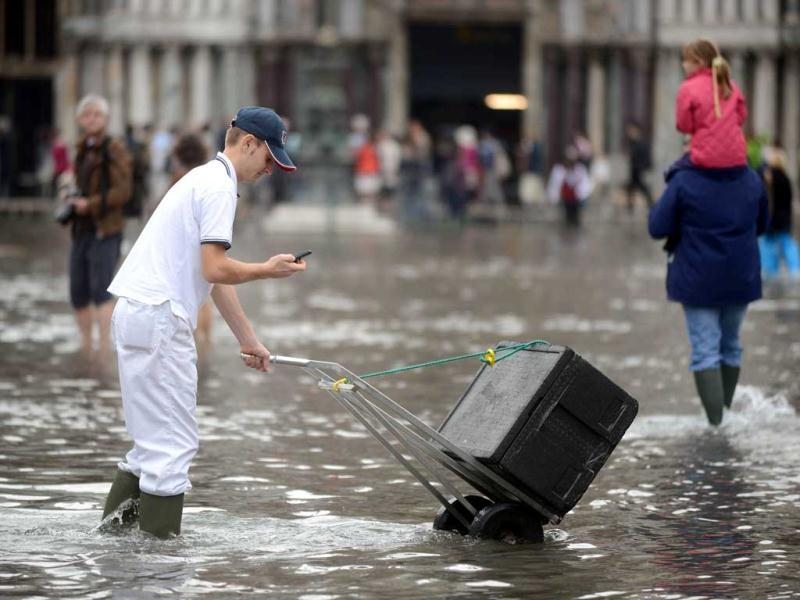 An employee walks on the flooded St Mark's square as he delivers goods during the first
