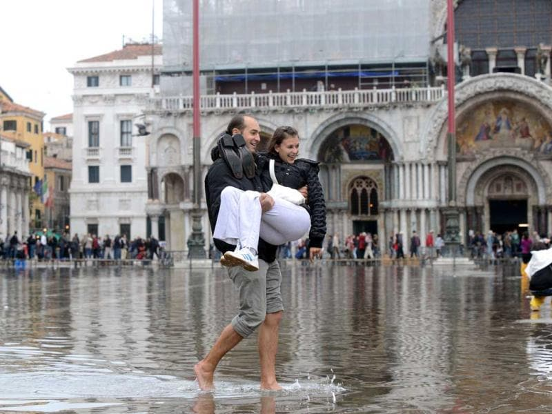 A tourist holds his partner in his arms on a flooded St Mark's square during the first