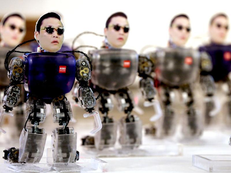 Robot models with faces attached with portraits of South Korean rapper Psy, who sings the popular 'Gangnam Style' song, perform the dance during a contest for reports of future strategies of robots in Seoul, South Korea. AP/Yonhap, Park Dong-joo