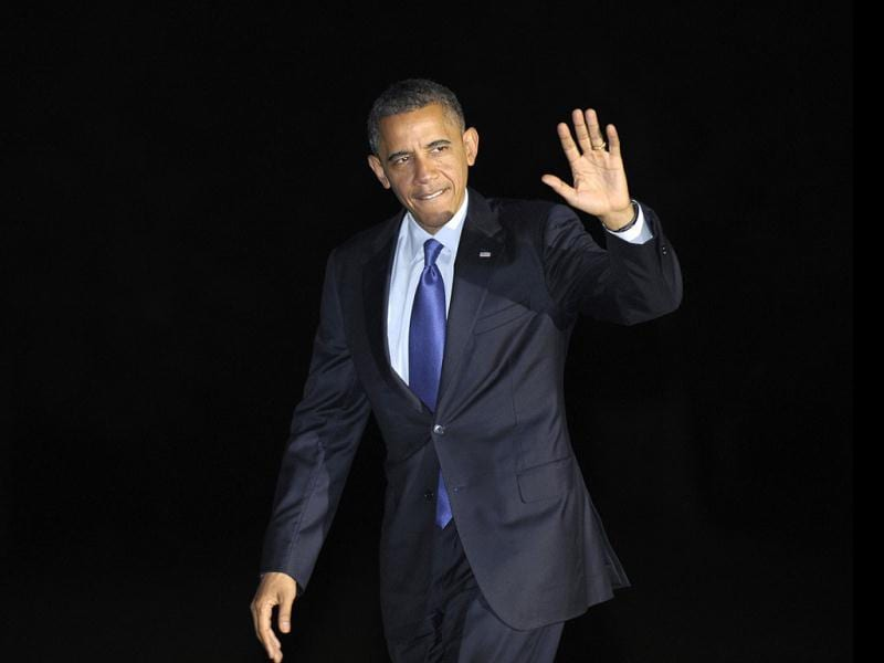 President Barack Obama waves as he returns to the White House in Washington after campaigning in Iowa and Ohio. AP photo