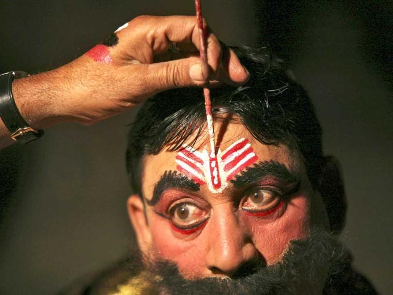 Kulbhushan, 38, a performer, gets makeup applied backstage before performing the role of the demon king Ravan in ramleela as part of Dussehra festival celebrations in Jammu. Reuters Photo