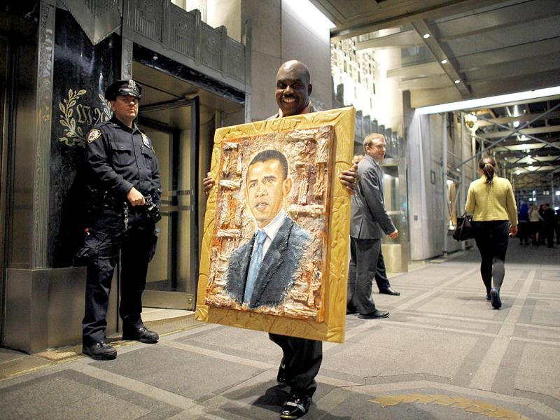 A man carries a painting of US President Barack Obama, to be donated to him as a gesture of support for his administration, outside the Waldorf Astoria hotel in New York. Reuters